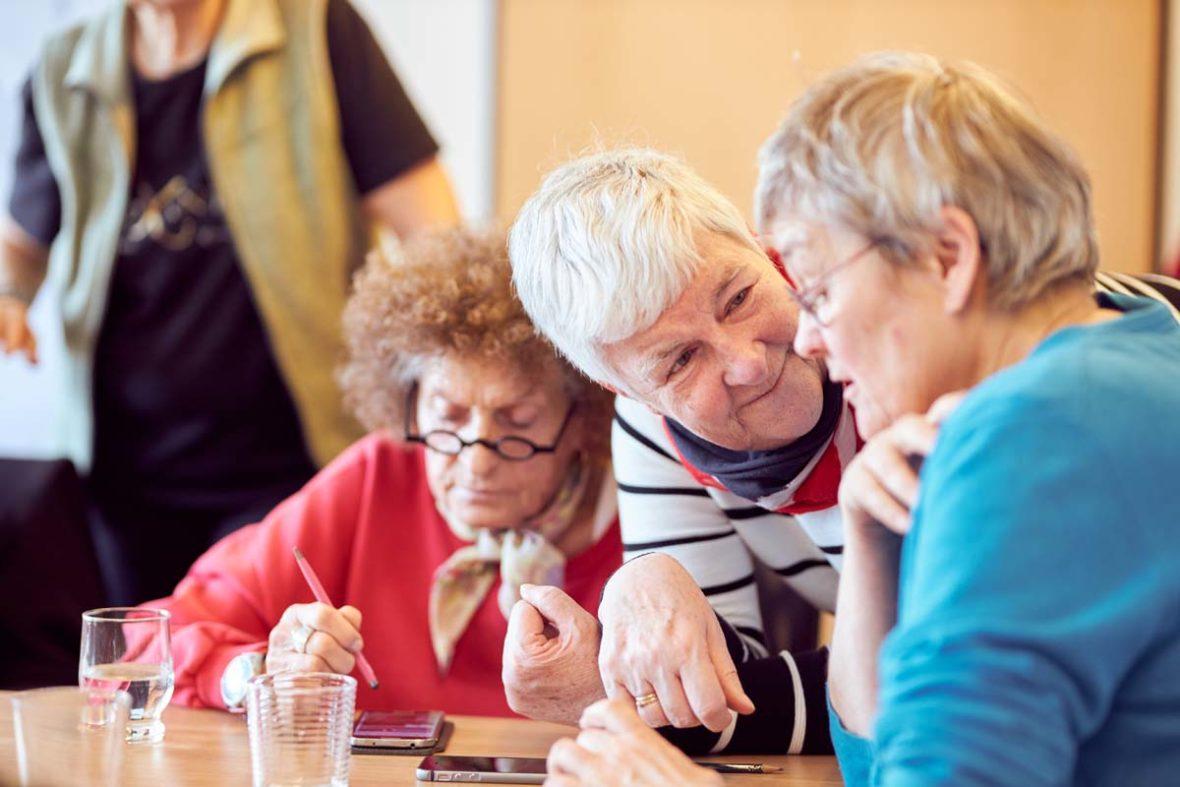 Dagmar Hirche lehnt sich auf den Tisch und spricht mit einer Teilnehmerin. Hinter ihr sitzt eine Frau in rotem Pulli, die mit einem Touch-Stift auf ihr Handy tippt.