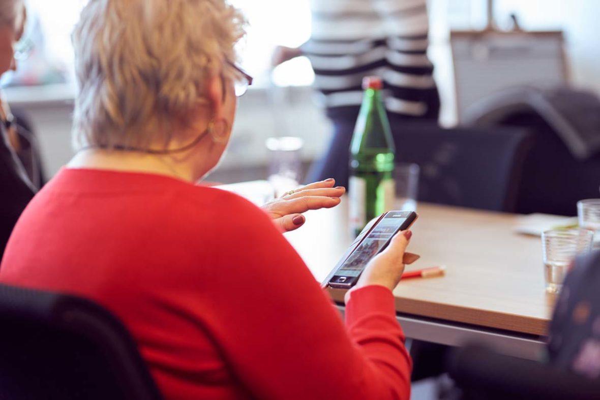 Eine ältere Dame von hinten, sie blickt auf ihr Smartphone und hält die linke Hand darüber.