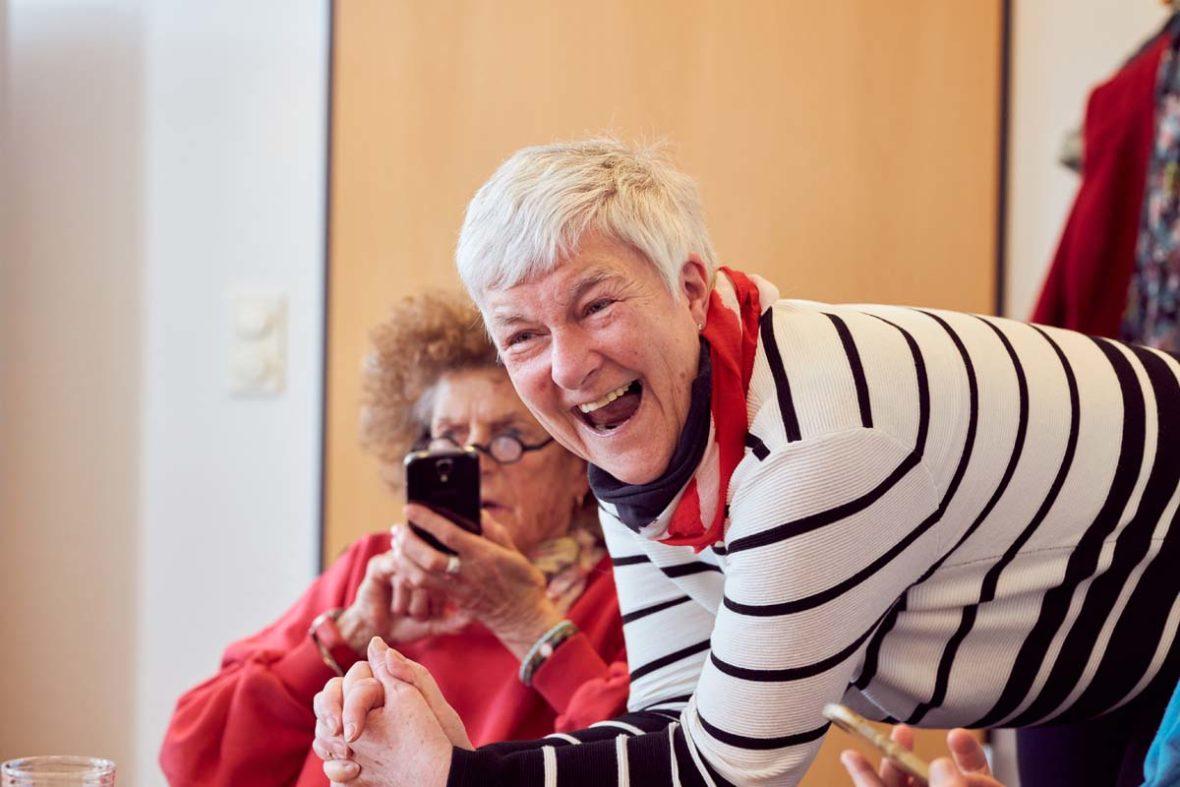 Dagmar Hirche lehnt auf dem Tisch und lacht herzlich. Hinter ihr sitzt eine Frau, die ihr Handy vor das Gesicht hält.