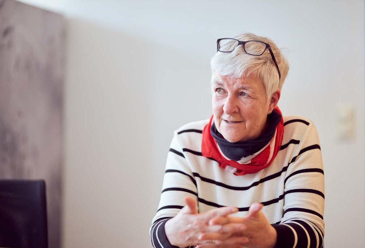 Dagmar Hirche trägt einen gestreiften Pulli und hat ihre Brille auf den Kopf geschoben. Sie spricht und hält die Hände dabei gestikulierend vor den Körper.