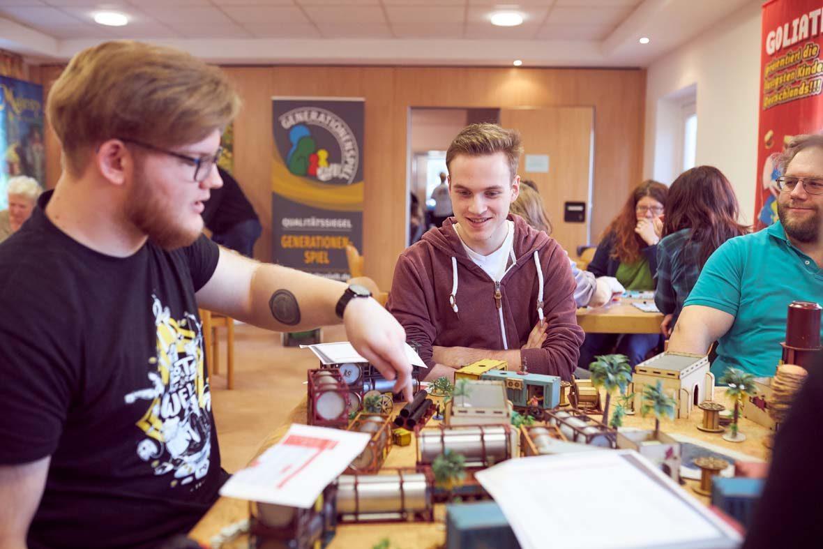 Eine gruppe junger Männer spielt ein Rollenspiel, auf dem Tisch steht eine richtige kleine Landschaft mit Plastikpalmen, Gebäuden und Containern.