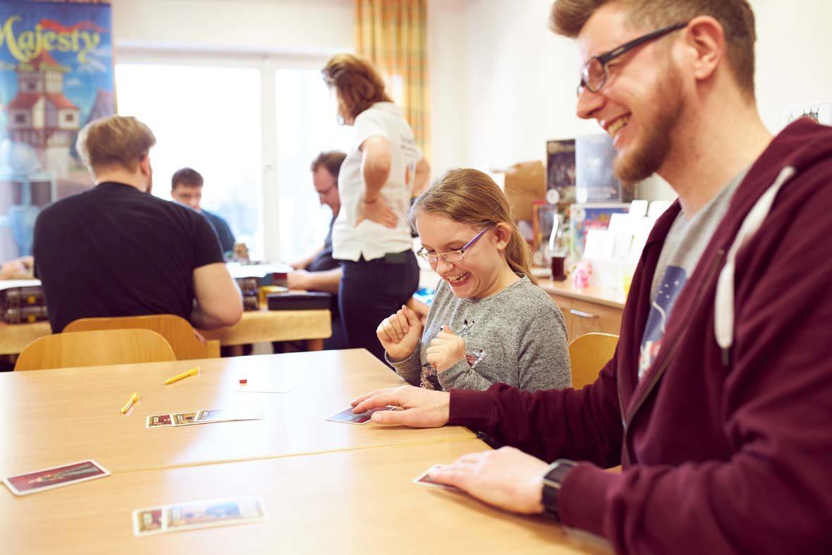 Ein junges Mädchen schaut aufgeregt auf seine Spielkarte, die ihm gerade hingeschoben wird. Es hält die Hände zu Fäusten geballt aufgeregt for der Brust.
