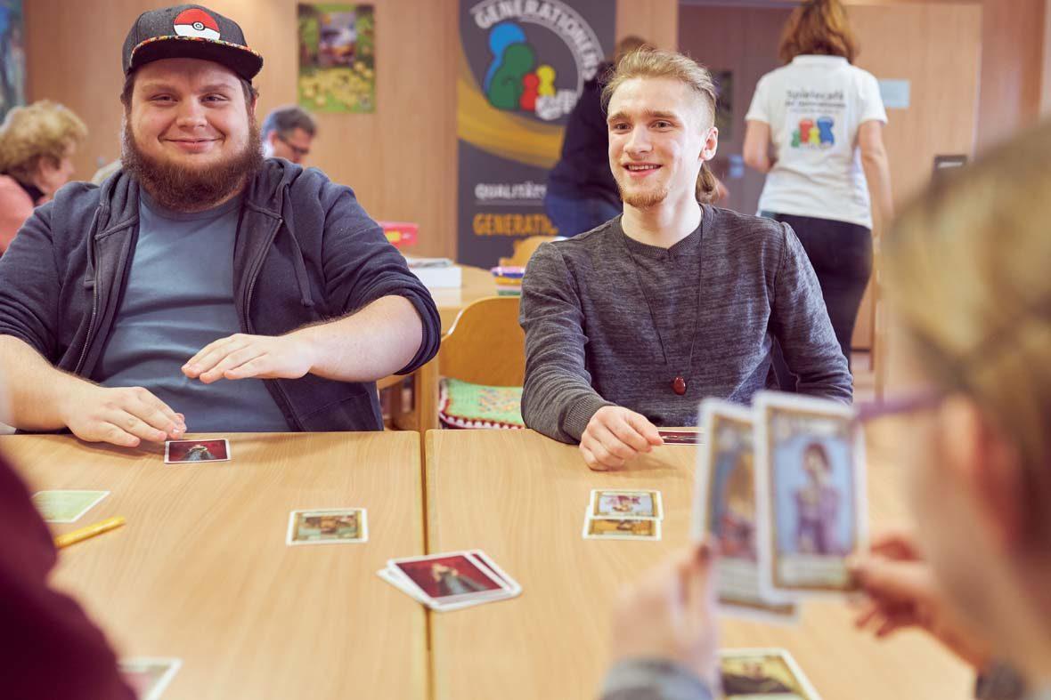 Zwei junge Männer sitzen am Tisch und spielen Karten, ihnen gegenüber sitzt ein junges Mädchen, dessen Kopf und Spielkarten verschwommen im Bild zu sehen sind.
