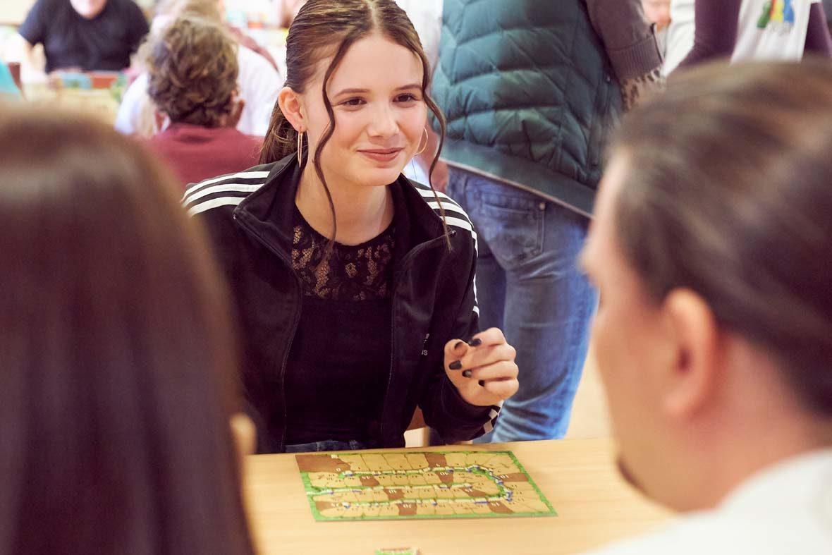 Eine junge Frau mit braunen Haaren und Pferdeschwanz sitzt vor einem kleinen Spielbrett. Sie schaut ihr Gegenüber lächelnd an.