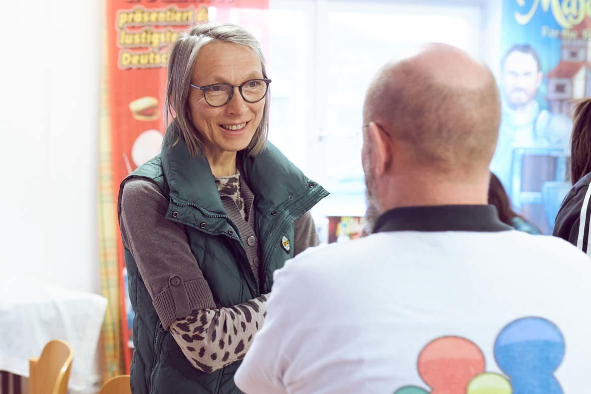 Eine Frau mit kinnlangen grauen Haaren und Brille unterhält sich mit einem Ehrenamtlichen des Vereins, der mit dem Rücken zur Kamera steht.