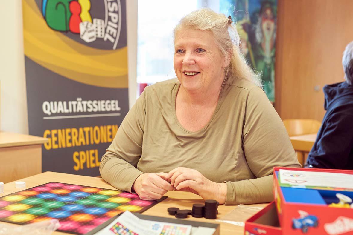 Eine ältere Frau mit blonden Haaren sitzt vor einem bunten Spielbrett. Sie schaut ihren Gegenüber an, den man im Bild aber nicht sieht.