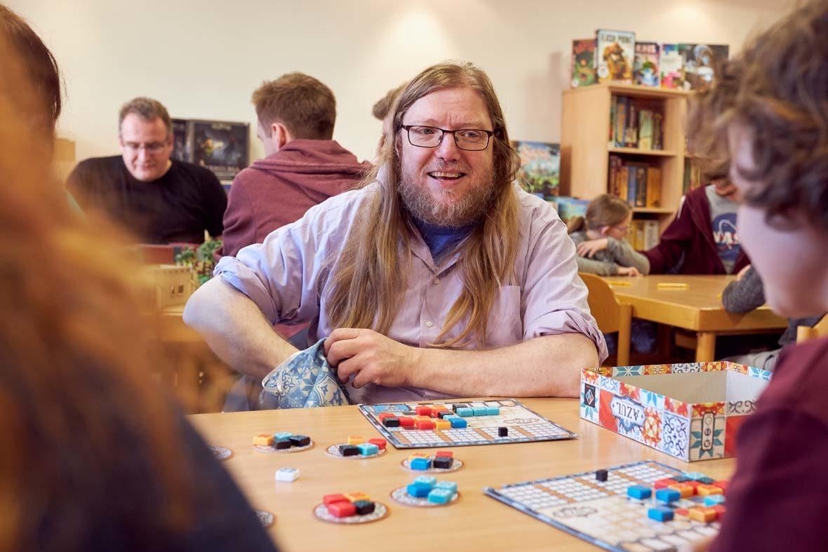 Ein Mann mit langen blonden Haaren und Brille greift in einen Beutel, vor ihm liegt ein Spielbrett und verschiedenfarbige, viereckige Steine.