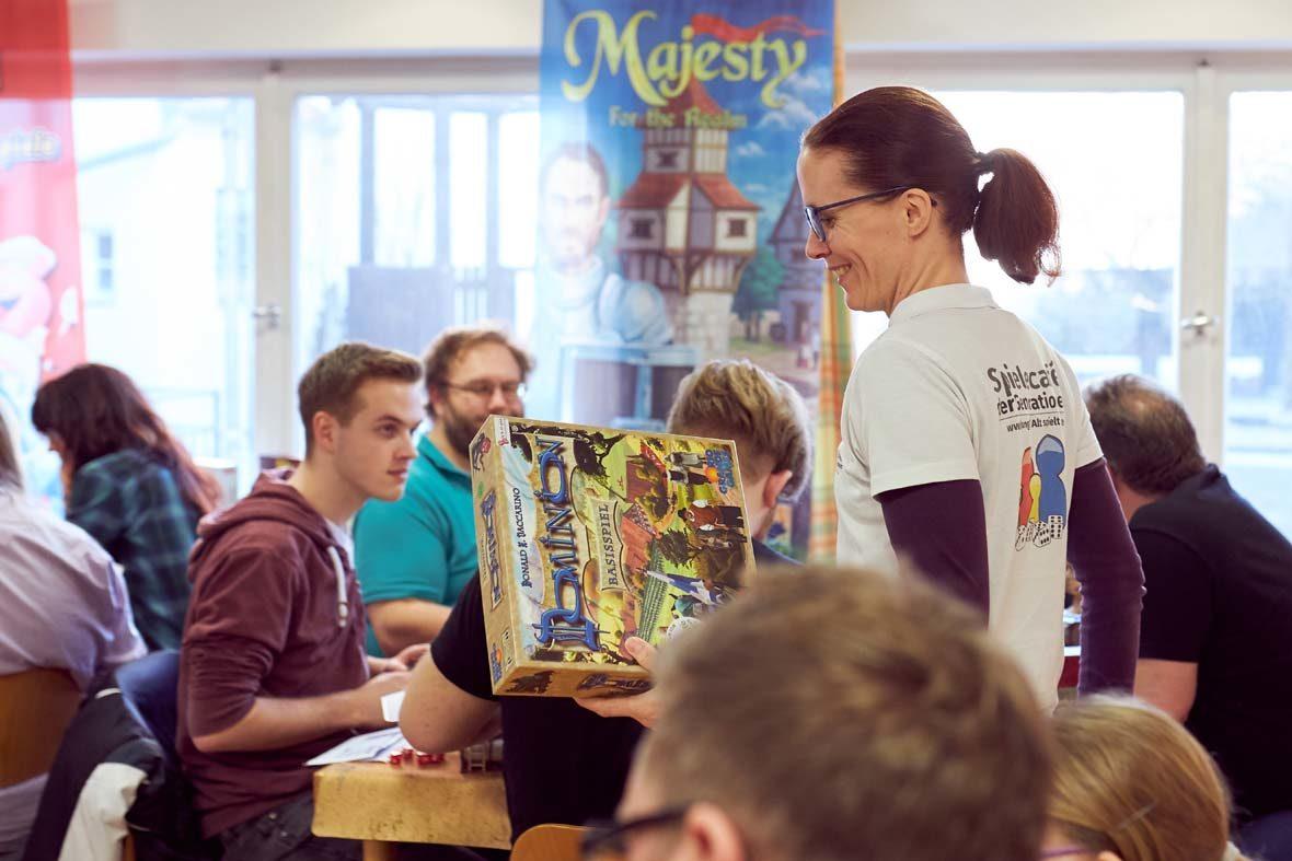 Petra Fuchs trägt ein Spiel durch das voll besetzte Spielecafé der Generationen.
