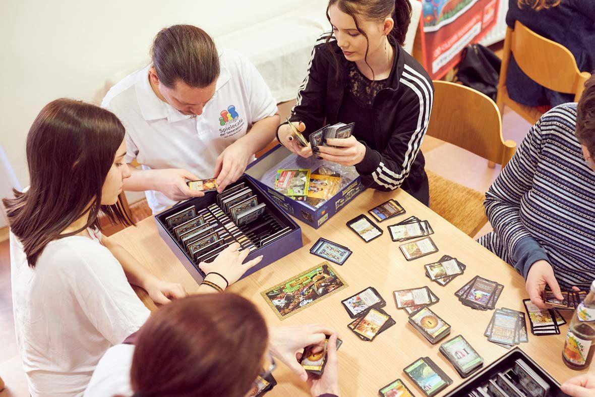 Eine Gruppe junger Menschen sitzt um einen Tisch, auf dem Tisch liegen Spielkarten.