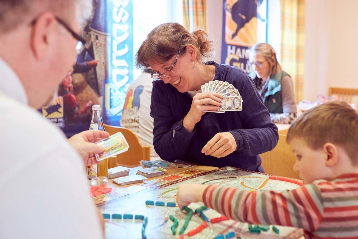 Eine Familie sitzt um ein Spielbrett, auf dem blaue, grüne und rote Plastikzüge in kleinen Schlangenlinien stehen. Ein kleiner Junge greift nach einem blauen Zug auf dem Brett. Die Mutter hält Karten in der Hand und lächelt.