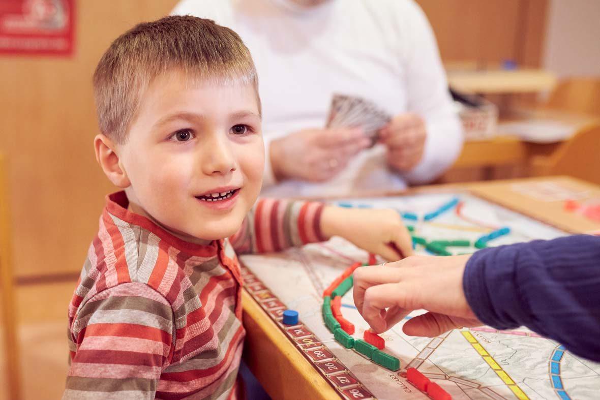 Ein kleiner Junge in gestreiftem Shirt sitzt vor einem Spielbrett, auf dem bunte Plastigzüge in Reihen stehen. Er schaut in die Kamera.