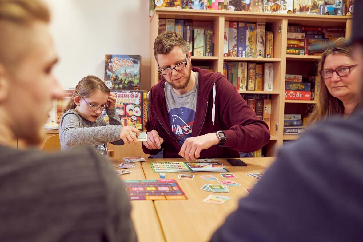 Ein junges Mädchen und ein junger Mann spielen ein Brettspiel, hinter ihnen ist ein Regal voller Spiele zu sehen.