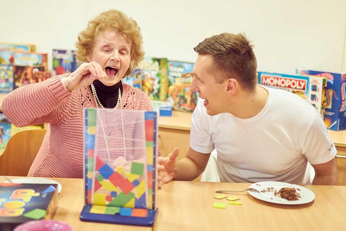 Mathilde sitzt vor dem Spiel Drop it und zielt mit offenem Mund, ihr Enkel Dennis feuert sie an. Vor ihm steht ein Stück Kuchen.