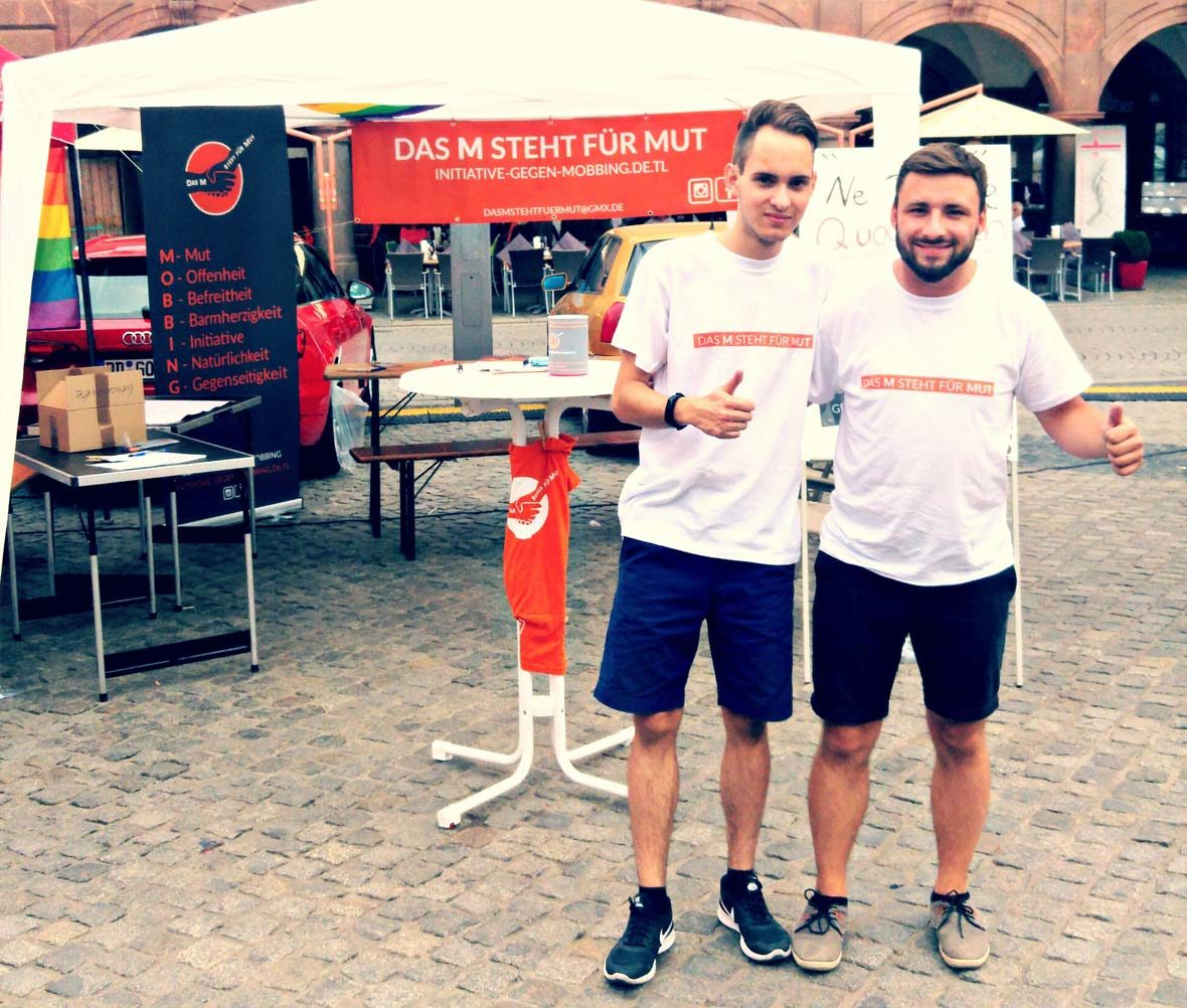 """Marco Krüger (rechts) und Stellvertreter Vincent Kunath (links) vor dem Stand des Vereins """"Das M steht für Mut"""""""