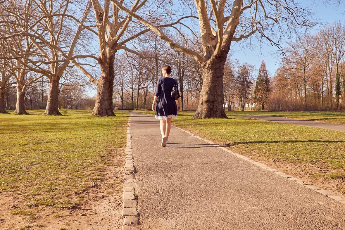 Eine Frau mit kurzen Haaren und Kleid läuft über einen schmalen Asphalt-Weg. Links und rechts sind grünes Gras und ein paar Bäume.