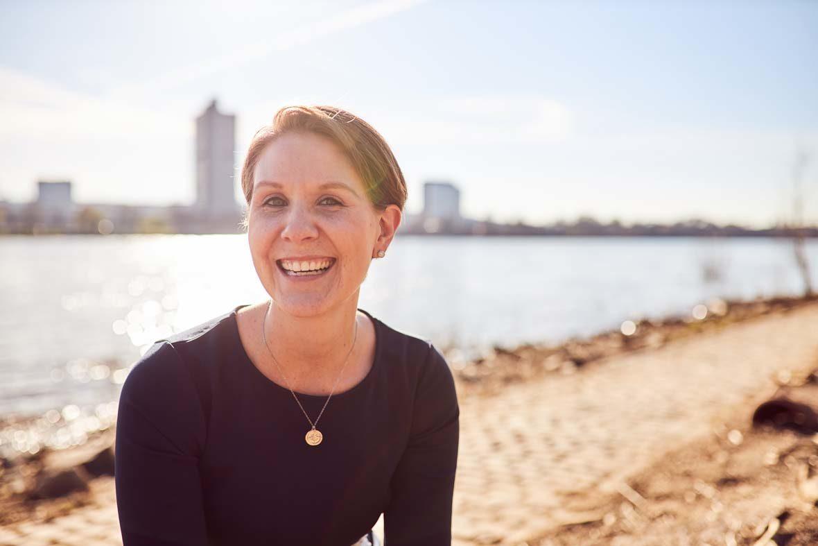 Eine junge Frau mit kurzen Haare lacht in die Kamera. Hinter ihr ist Wasser, neben ihr Strand.
