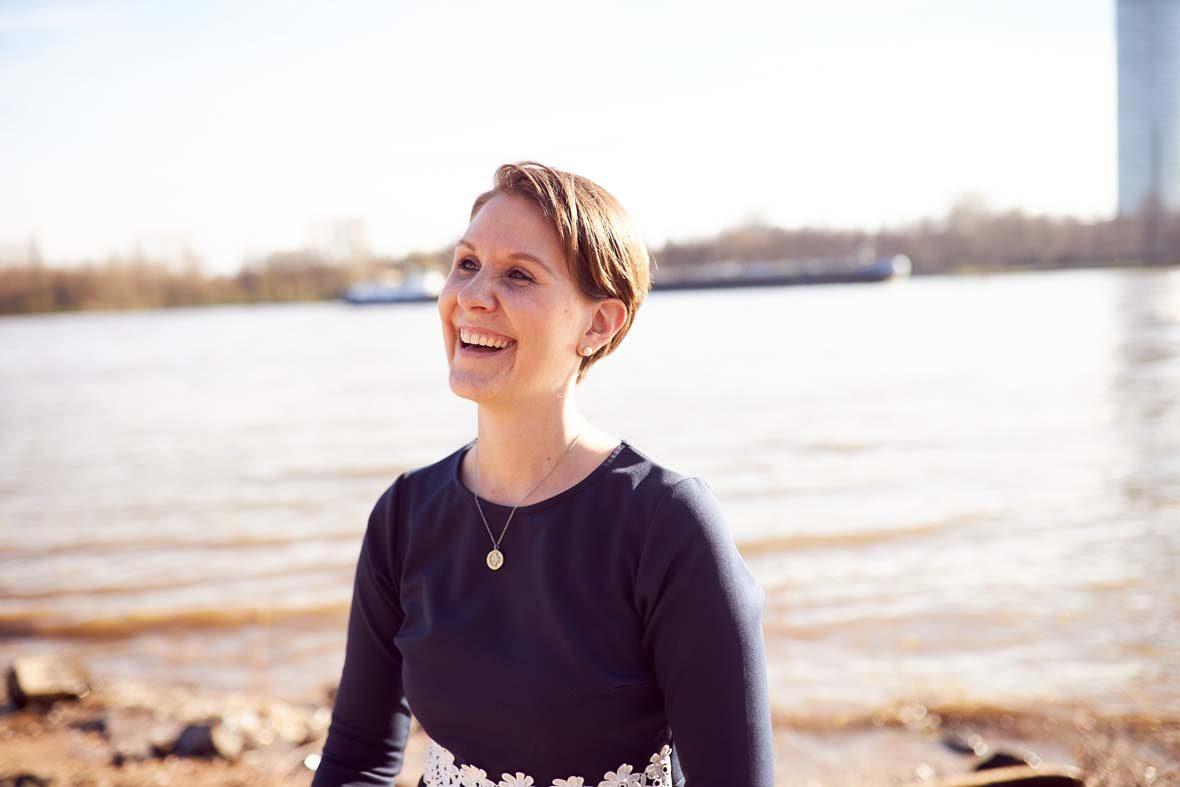 Eine Frau mit kurzen, braunen Haaren blickt links aus dem Bild heraus und lacht.