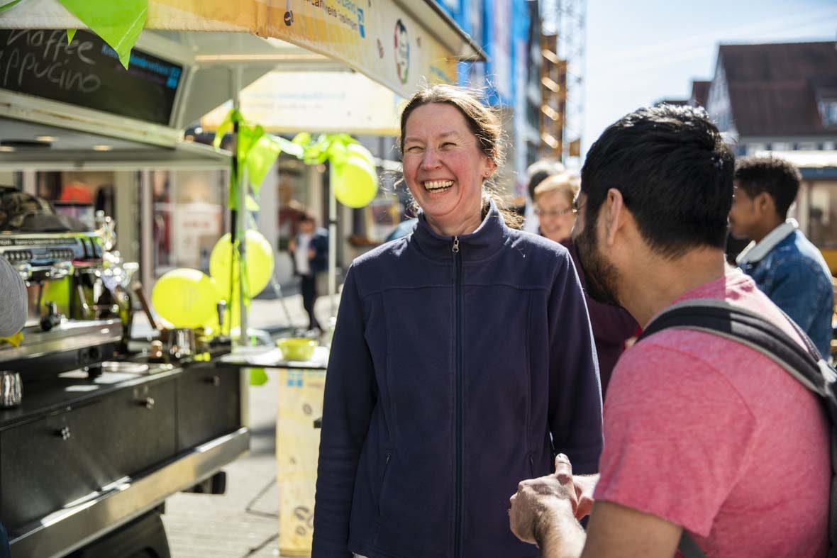 Eine Frau mit Zopf lacht herzlich. Neben ihr steht ein junger Mann in T-Shirt, mit dem sie sich unterhält. Hinter ihr sieht man das Café-Tee-Mobil, das mit Luftballons geschmückt ist.
