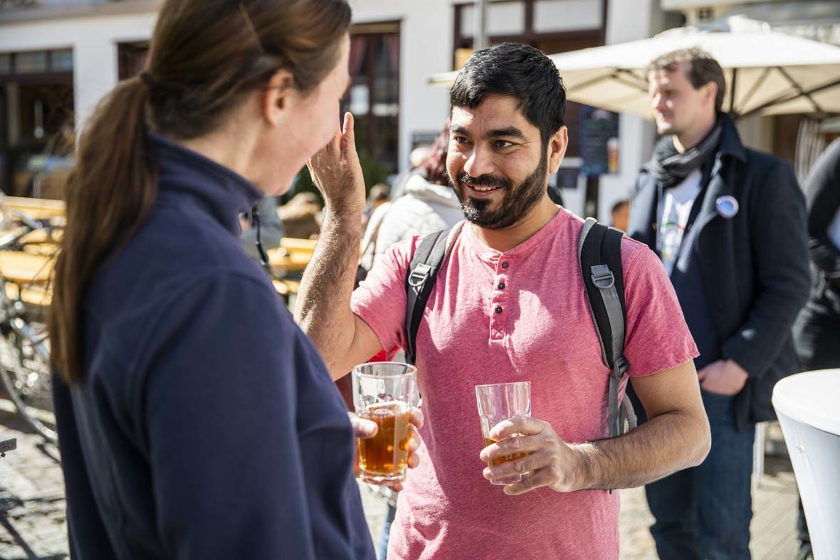 Ein junger Mann spricht mit einer Frau, er gestikuliert mit der rechten Hand und hält in der linken Hand ein Glas mit Tee. Der Mann lächelt.