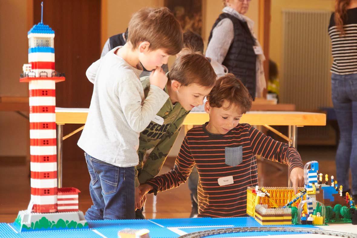 Drei Jungs schauen sich ein LEGO-Gebäude an. Neben ihnen steht außerdem ein LEGO-Leuchtturm.