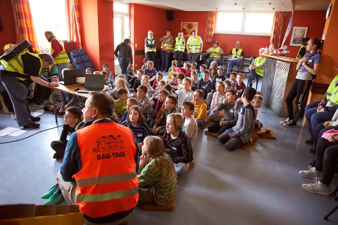 Kinder sitzen auf dem Boden, um sie herum erwachsene Helfer mit Warnwesten.