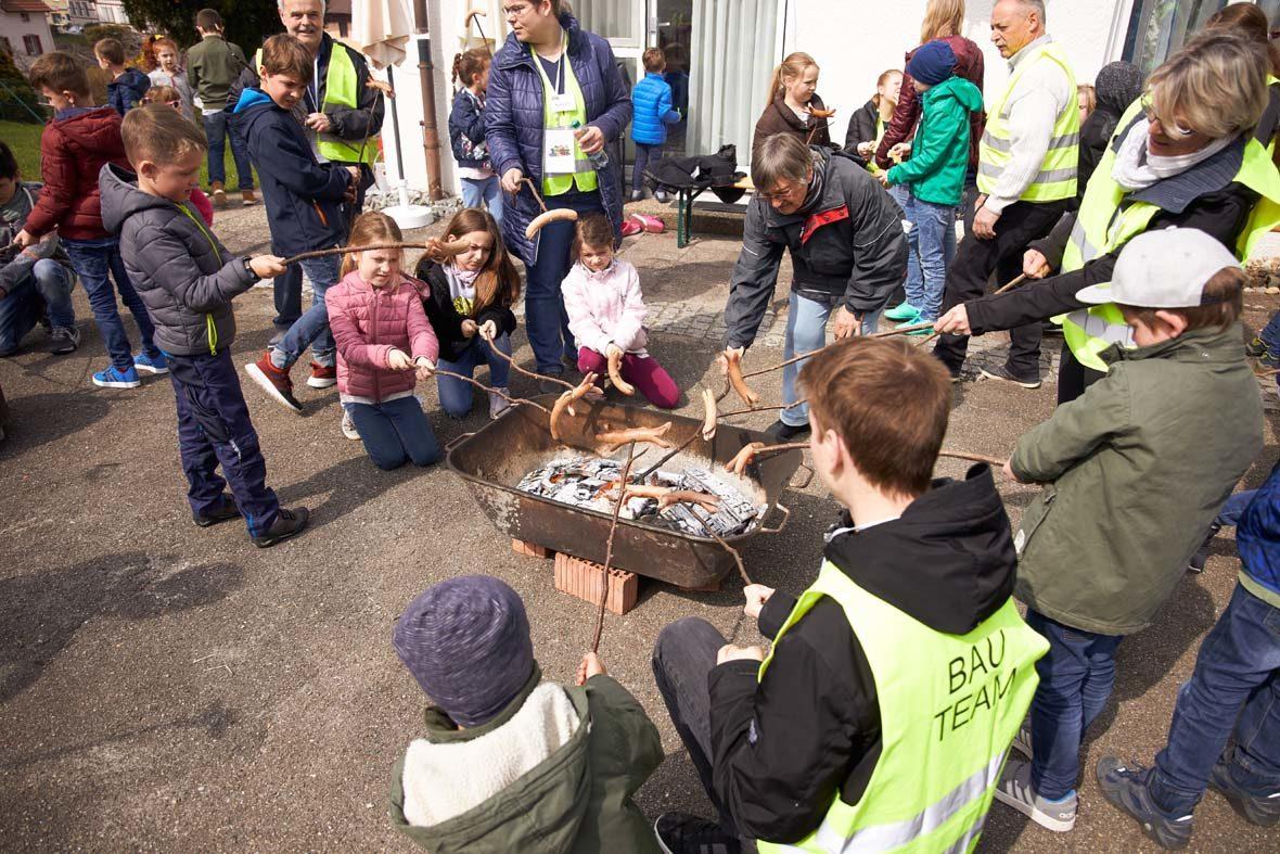 In einer eisernen Wanne ist glühende Kohle, um sie herum stehen Kinder mit Würstchen am Stock und halten sie über die Kohle.
