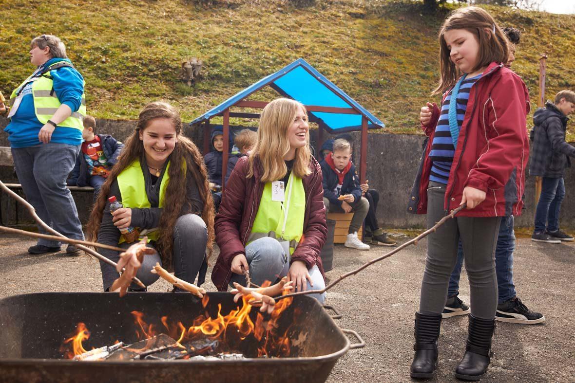 In einer eisernen Wanne ist glühende Kohle und Feuer, ein Mädchen steht rechts daneben und hält ein Würstchen am Stock darüber. Zwei Frauen in Warnweste knien vor der Wanne und eine schaut das Mädchen lachend an.