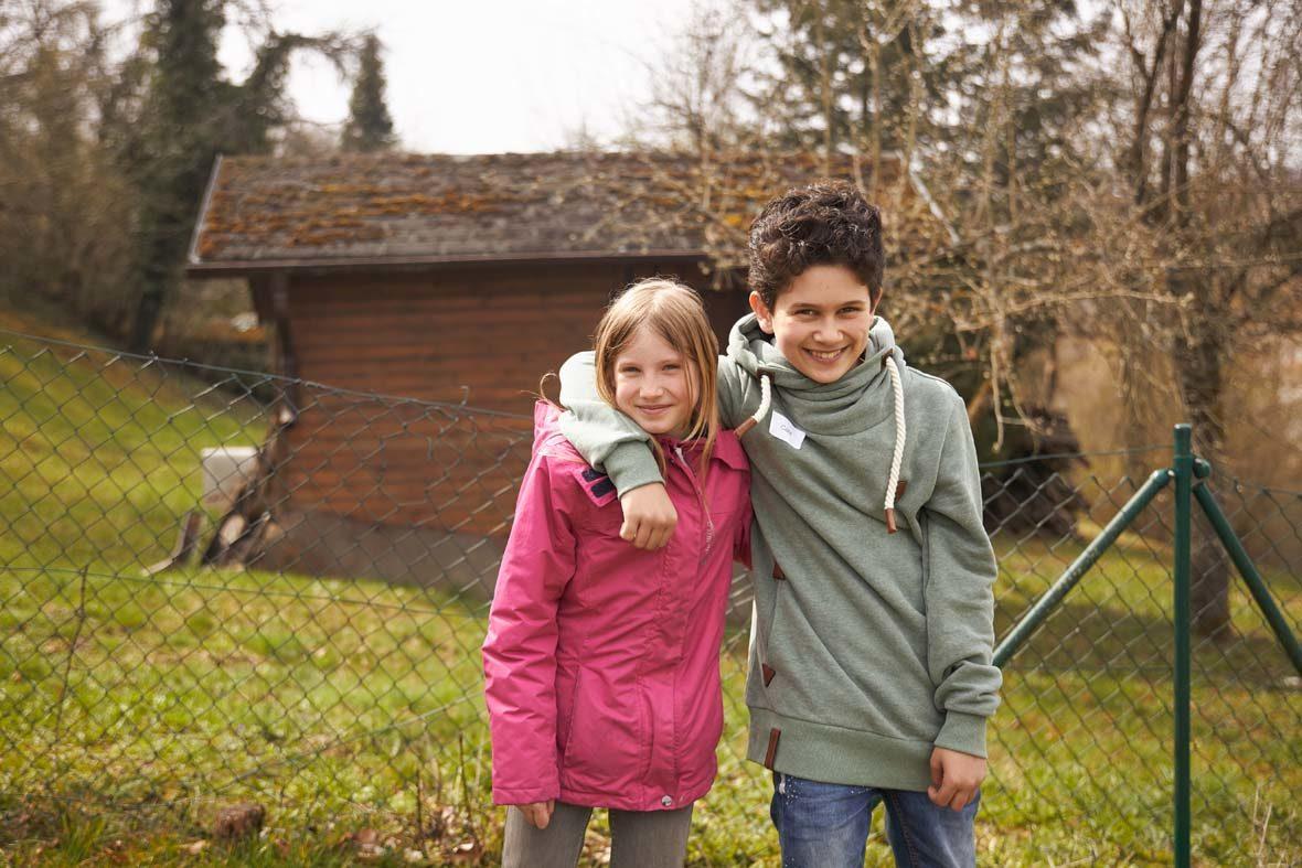 Ein Junge hat freundschaftlich den Arm um ein Mädchen gelegt. Sie schauen beide in die Kamera und lächeln.