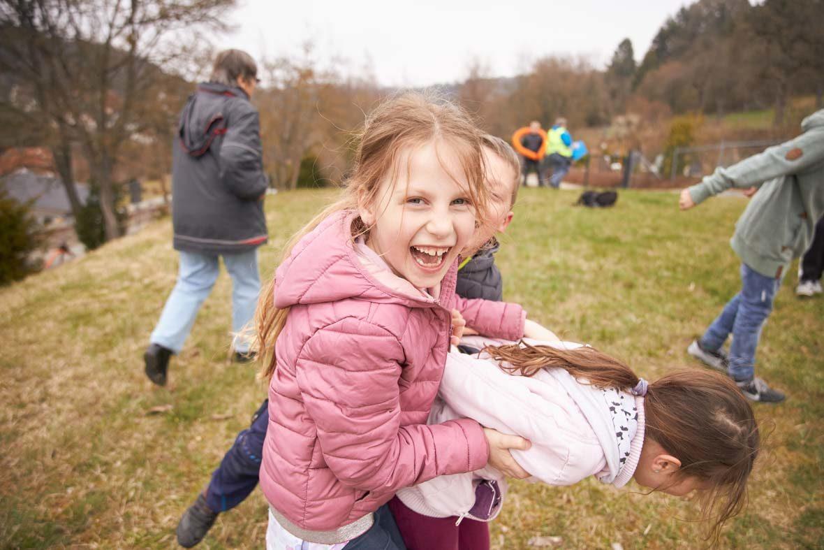 Ein Mädchen schaut lachend in die Kamera, es hält ein anderes Mädchen im Spiel fest, das sich nach vorne beugt.