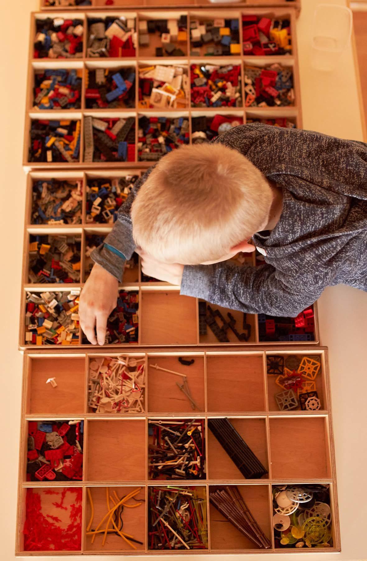 Blick von oben: Ein blonder junge lehnt über Holzkästen, in denen verschiedene LEGO-Steine sortiert gelagert sind. Er greift in eines der Kästchen.