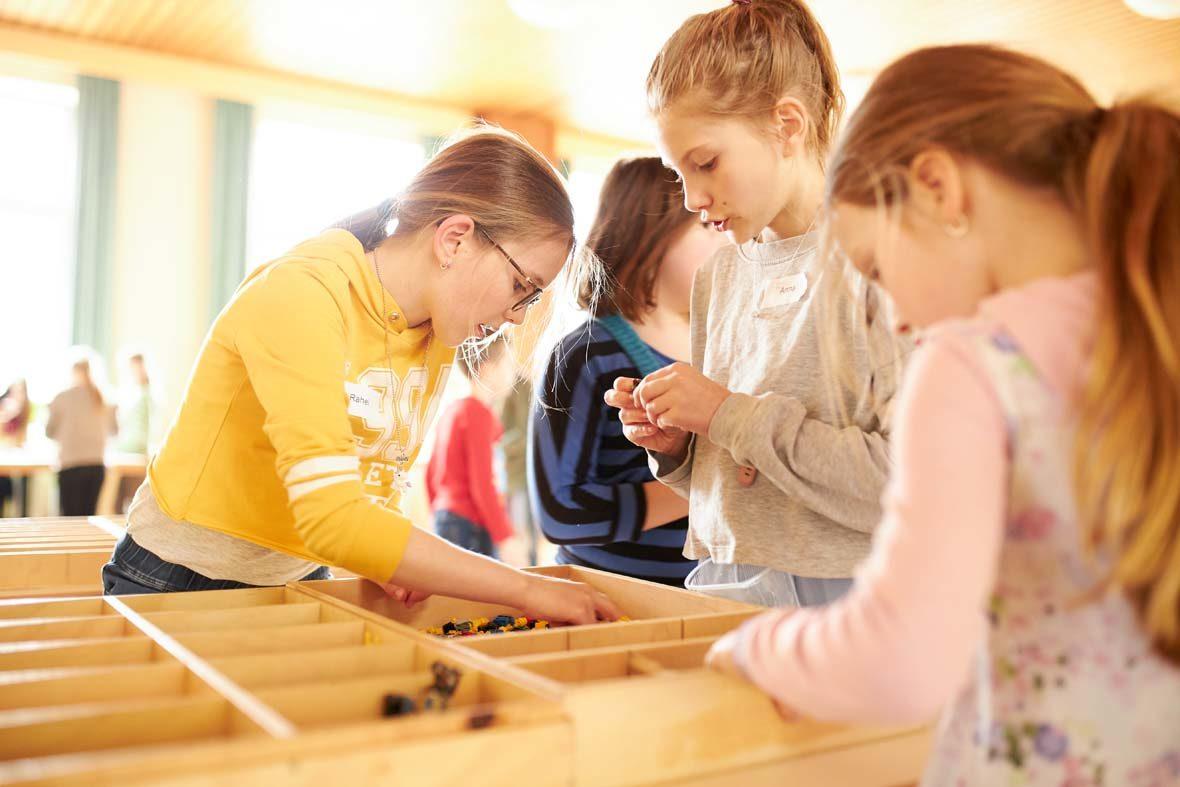 Drei Mädchen schauen in den Holzboxen mit LEGO-Steinen nach passendem Baumaterial.