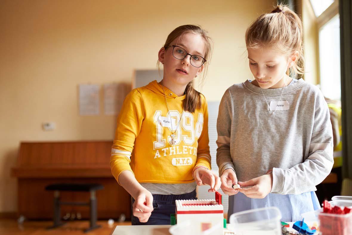 zwei Mädchen bauen an einem LEGO-Haus.