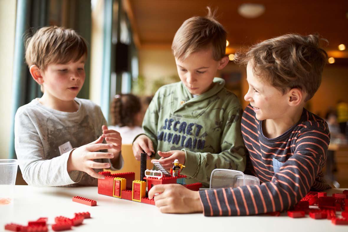 Drei Jungs bauen mit LEGO-Steinen ein Gebäude.