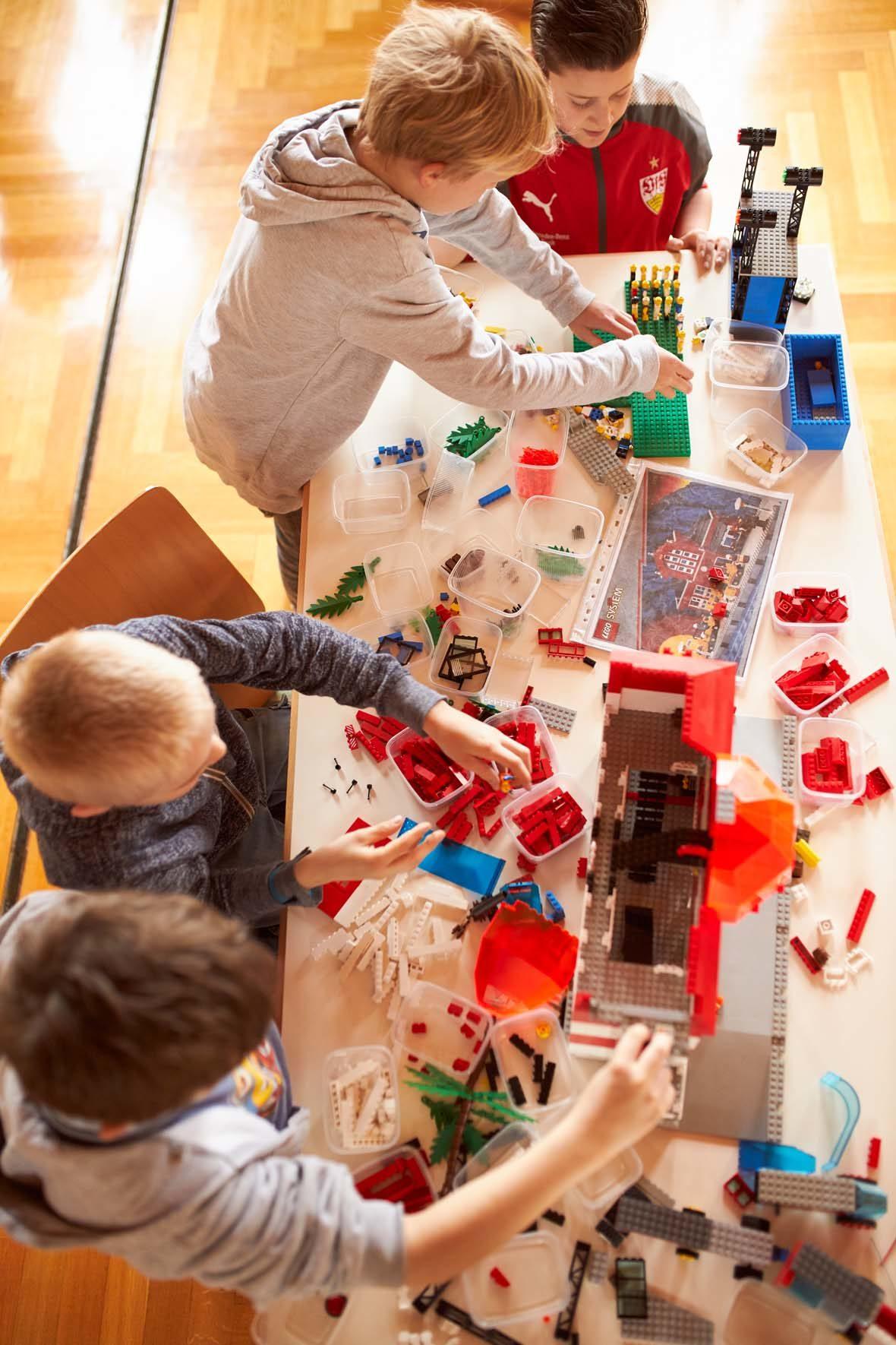 Blick von oben auf einen Tisch, dort liegen sehr viele LEGO-Steine verstreut und auch in Plastikbehältern herum. Vier Jungen bauen mit den Steinen zwei Gebäude.