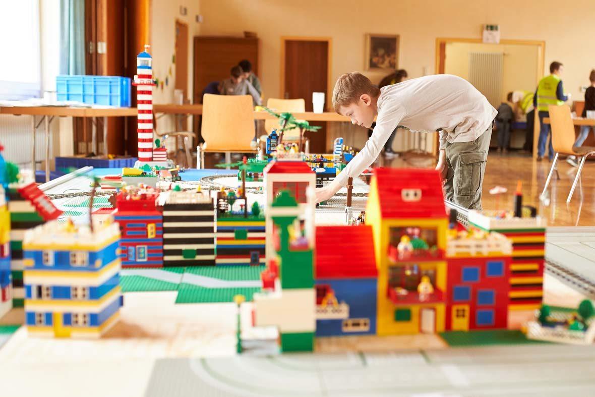 Eine LEGO-Stadt ist auf dem Bild zu sehen, im Hintergrund ein Junge, der sich darüber beugt und noch etwas baut. Weiter hinten sieht man Tische, Stühle und andere Personen.