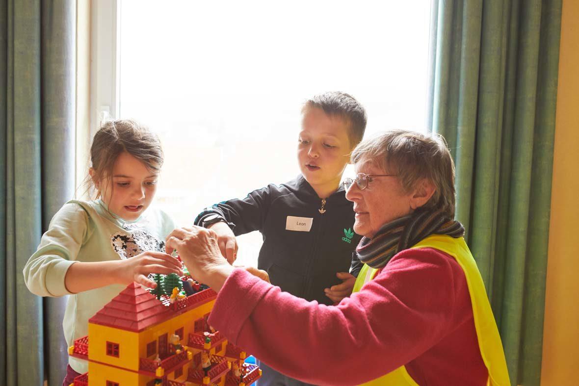 Ein Mädchen, ein Junge und eine Helferin bauen an einem großen, gelben LEGO-Haus.