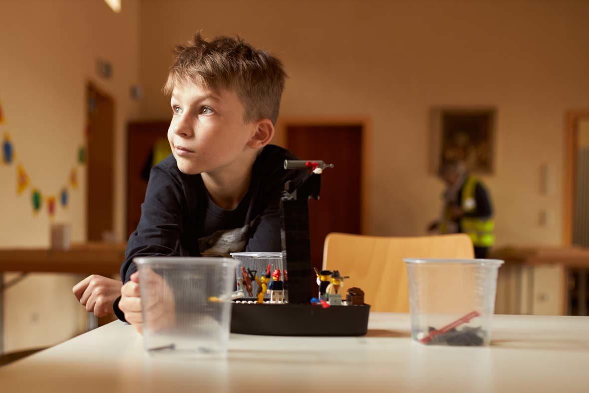 Ein Junge sitzt vor einer LEGO-Konstruktion und schaut in eine andere Richtung.
