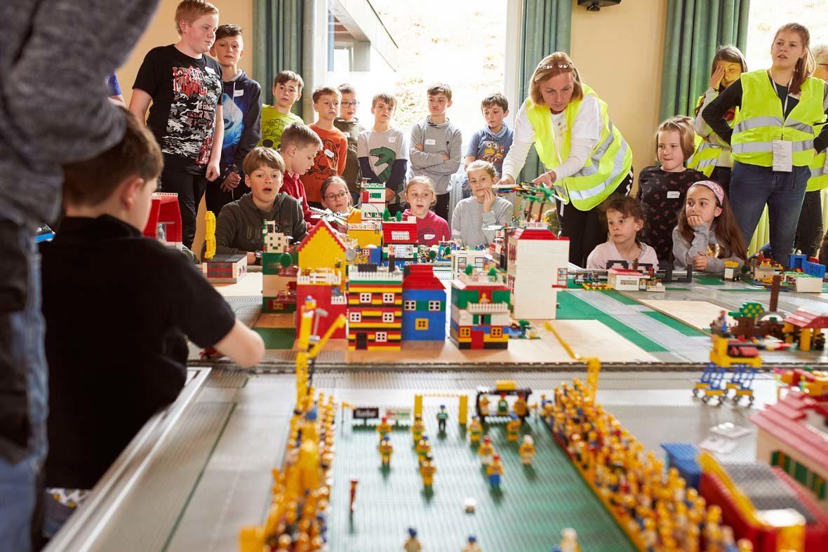 Die Kinder sitzten gemeinsam vor der von ihnen gebauten Stadt aus LEGO-Steinen.