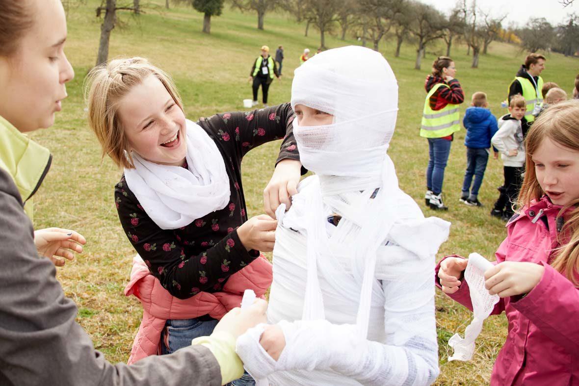 Zwei Mädchen und eine Helferin wickeln ein anderes Mädchen mit Verband ein, damit es aussieht wie eine Mumie.