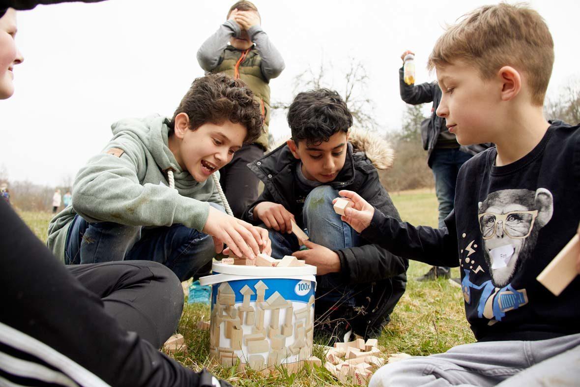 Drei Jungs sitzen vor einem Eimer mit Holzklötzen, die sie zum Teil auf der Wiese ausgebreitet haben. Im Hintergrund stehen zwei weitere Jungs, die aber nicht gut zu erkennen sind.