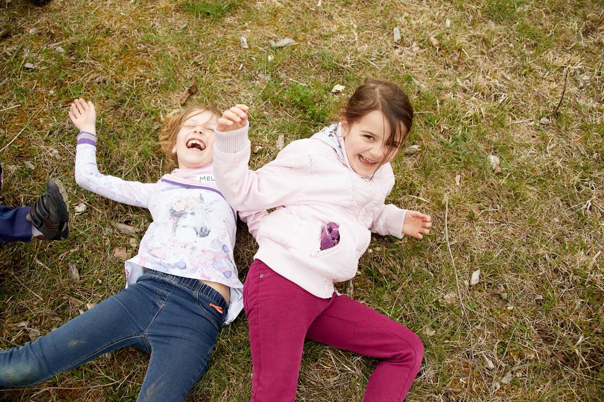 Zwei Mädchen kugeln sich lachend über das Gras.