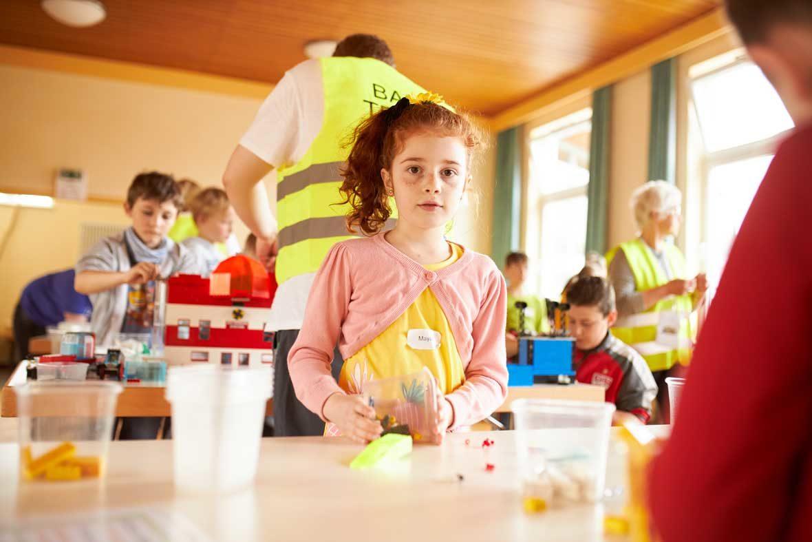 Ein Mädchen steht am Tisch und hält eine Plastikbox mit LEGO-STeinen in der Hand. Hinter ihr stehen Menschen, die an LEGO-GEbäuden bauen.
