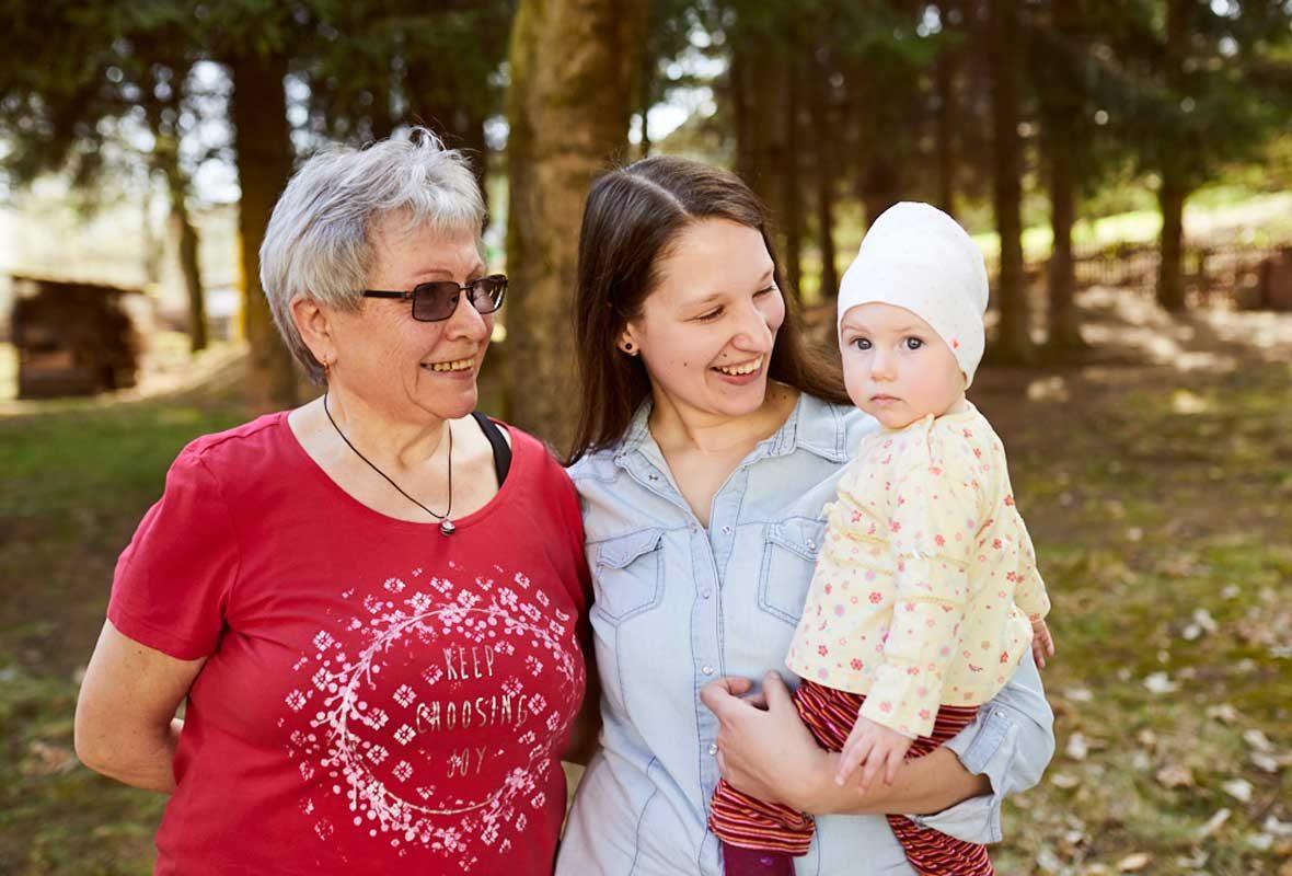 Eine ältere Frau steht neben einer jüngeren Frau, die ein Kind auf dem Arm hält.