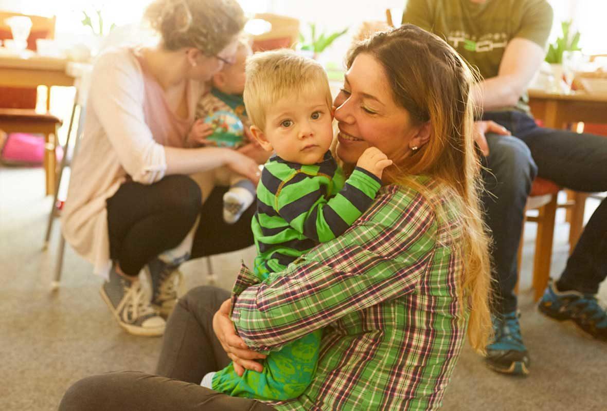 Junge Frau sitzt auf dem Boden und hält ein Kind liebevoll im Arm.