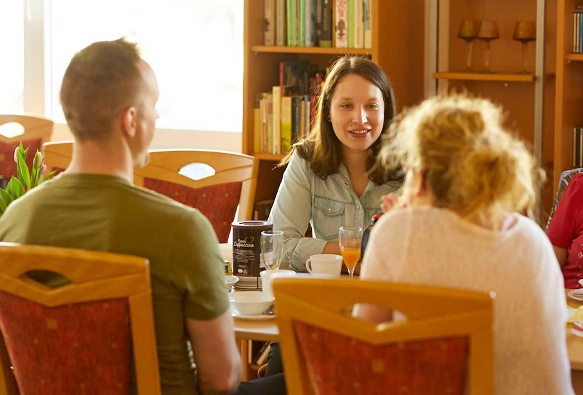 Zwei junge Frauen und ein Mann sitzen am Tisch und unterhalten sich.