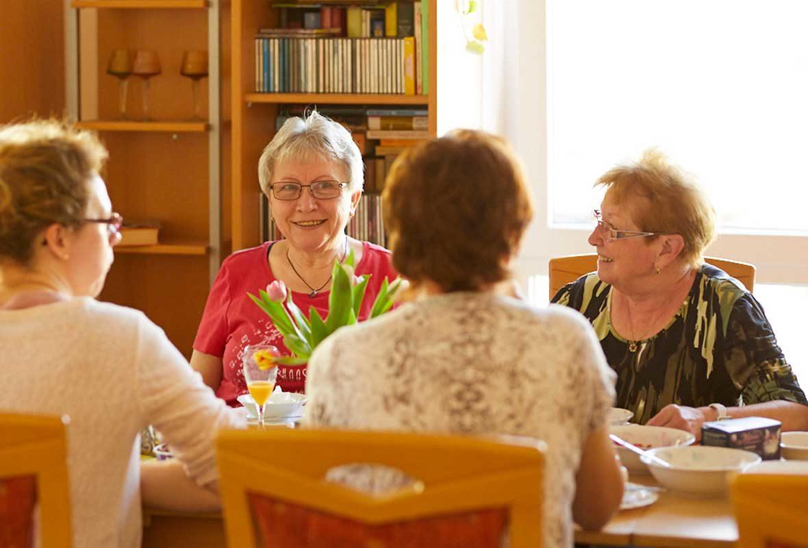 Vier Frauen sitzen am Tisch und unterhalten sich.