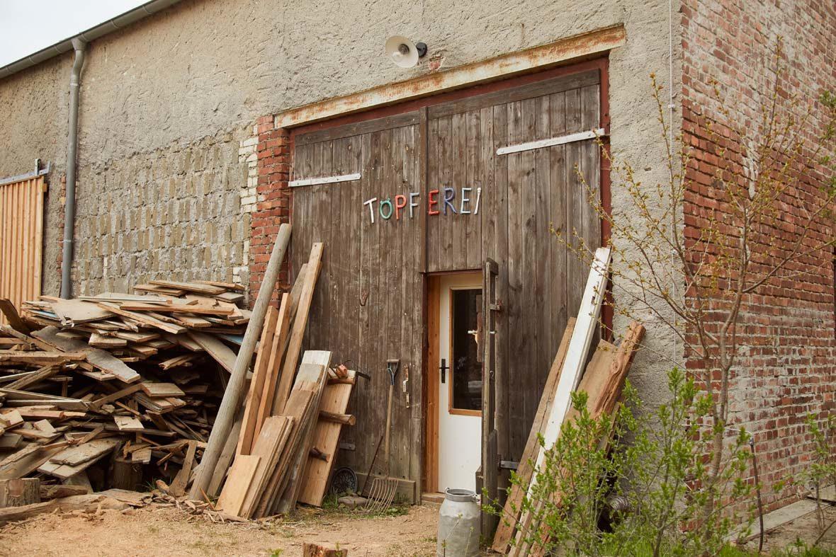 Außenansicht Gebäude mit großem Holztor, auf dem Töpferei steht.