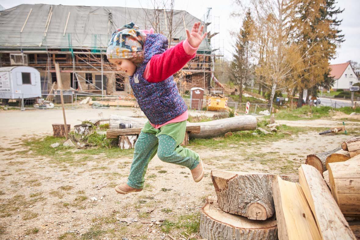 Junges Mädchen springt von einem Holzklotz.