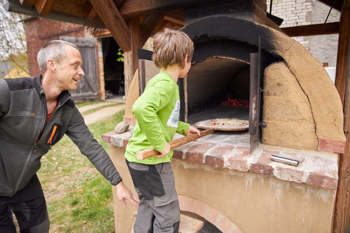 Kleiner Junge steht am Lehmbackofen und schiebt eine Pizza hinein, neben ihm steht ein Mann.