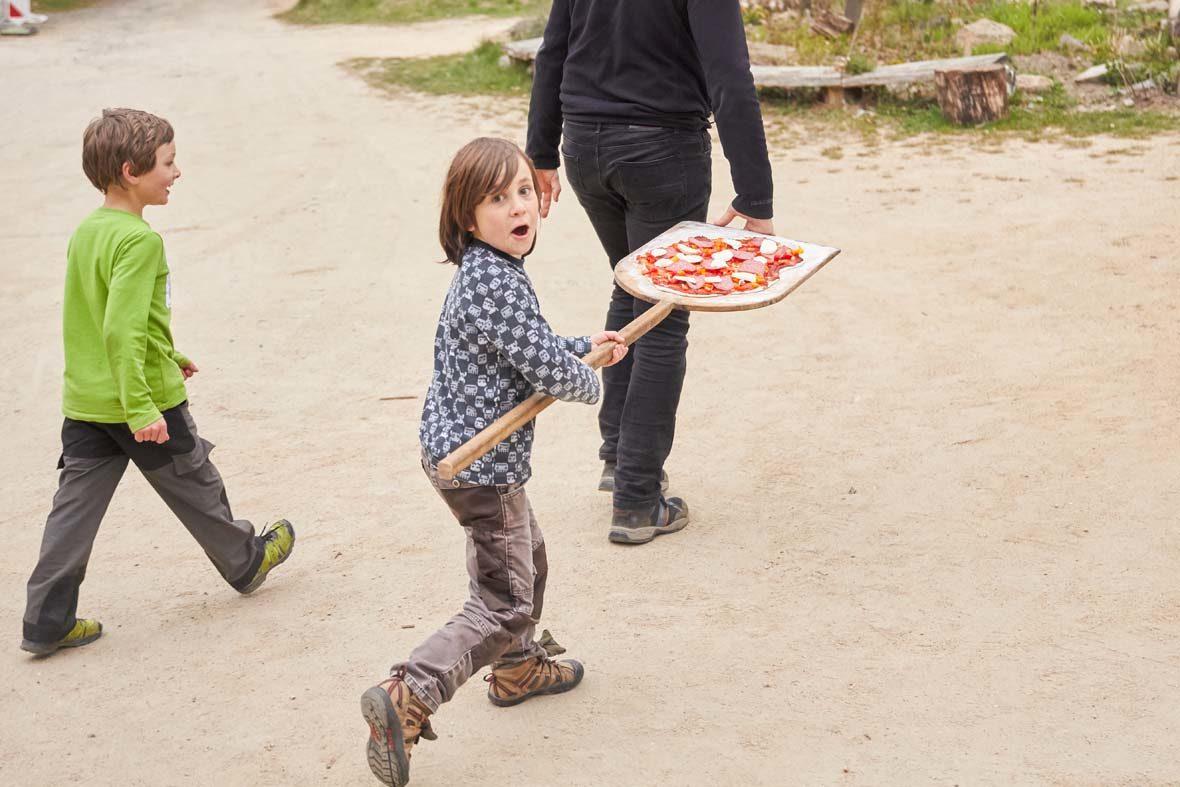Kleiner Junge trägt Pizza auf einem Holzschieber.
